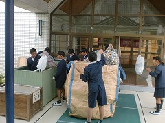集まったアルミ缶を子どもたちが袋から出して業者が用意してくださった袋に移し替えています