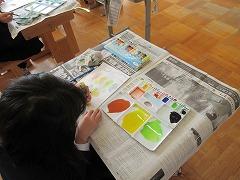 絵の具で作った色をペンの先につけて絵を描く様子